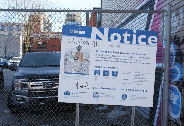 blue and white city of toronto development notice sign on a chainlink fence in front of a vacant lot wehre cars and trucks are parked. For 245 to 285 Queen Street East, Bridgen Place and Richond.