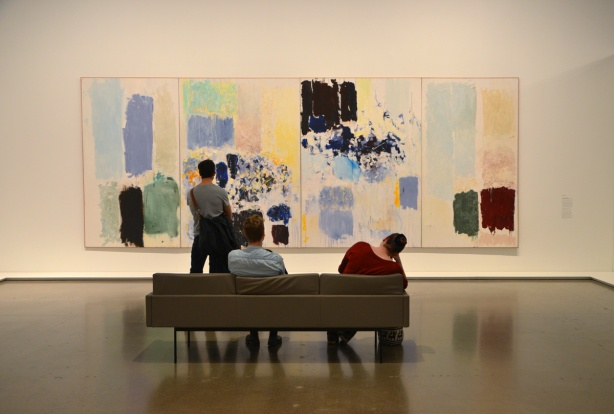 Three people are looking at a large Riopelle painting in an art gallery, two are sitting on a couch and the third is standing closer to the painting.