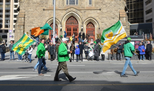 three men carrying flags in the St. Patricks day parade, walk past a church, many people on the sidewalk, pavement, watching the parade go by