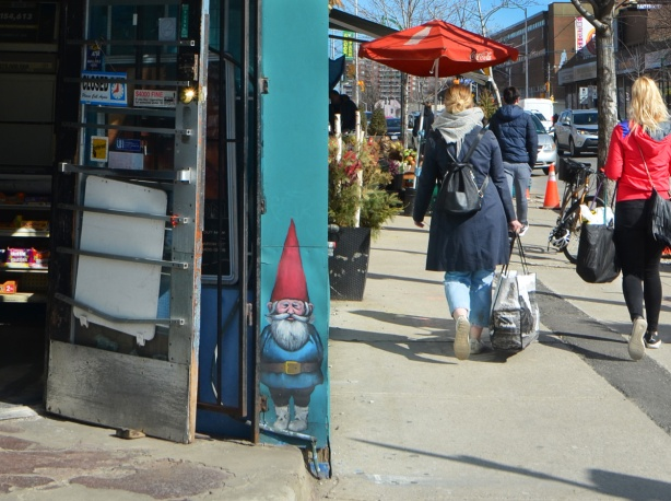 a small gnome painted on the wall beside a door to a convenience store. The door is open and people are walking past