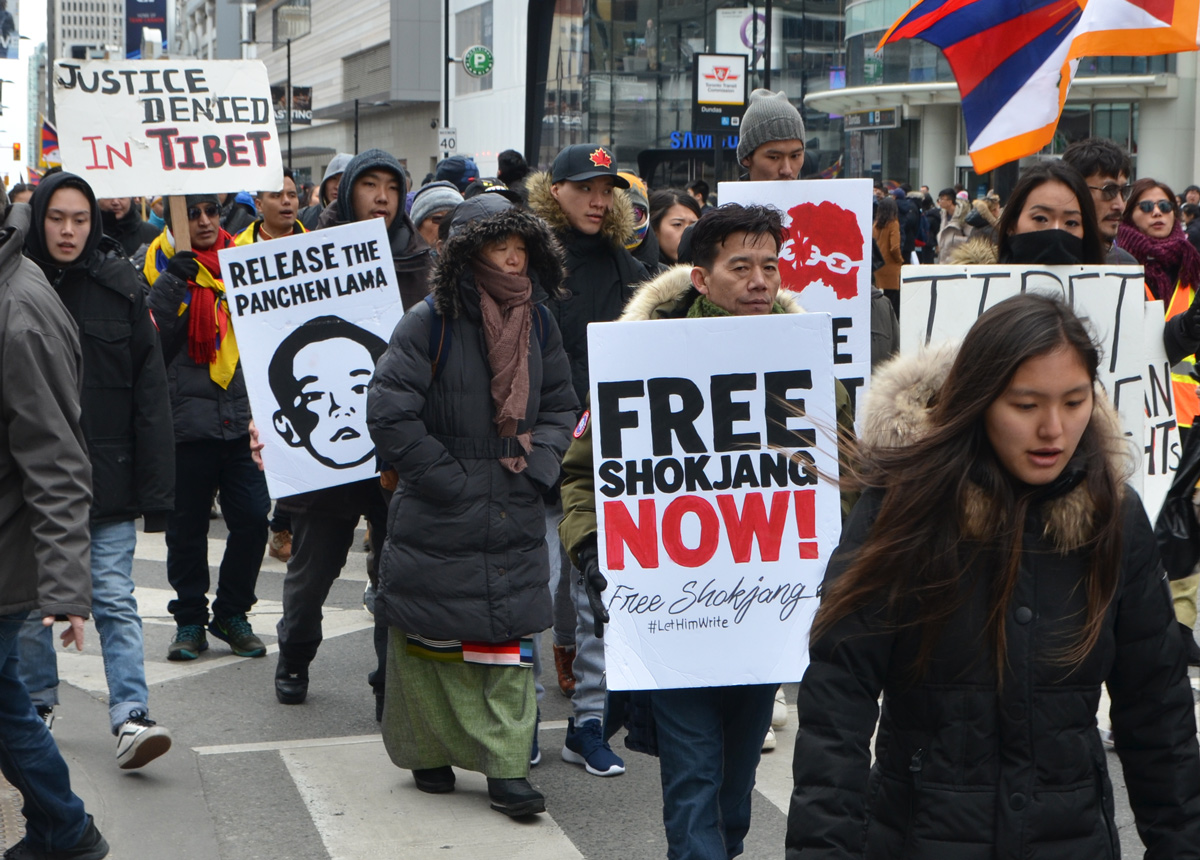 people carrying protest signs, free Shokjang now, release the panchen lama