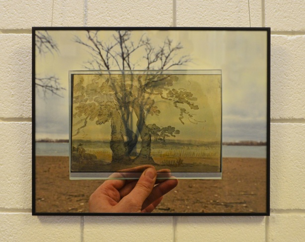 a photograph on a gallery wall, a hand holding a photo printed on glass in the middle of another photo, superimposed landscapes