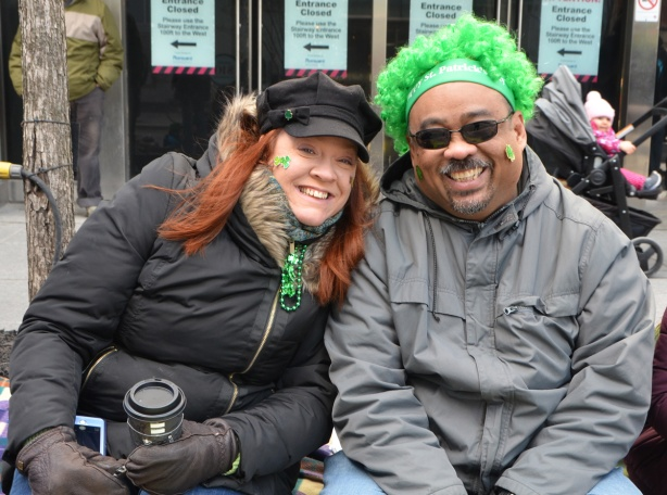 two people sitting on the sidewalk watching the St. Patricks Day parade, a red head woman with long hair and a man with a curly bright green wig, both are smiling, both dressed for cold weather,