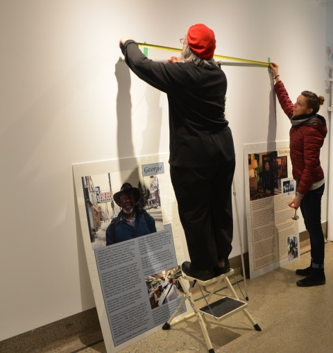 two people hanging pictures in an art gallery
