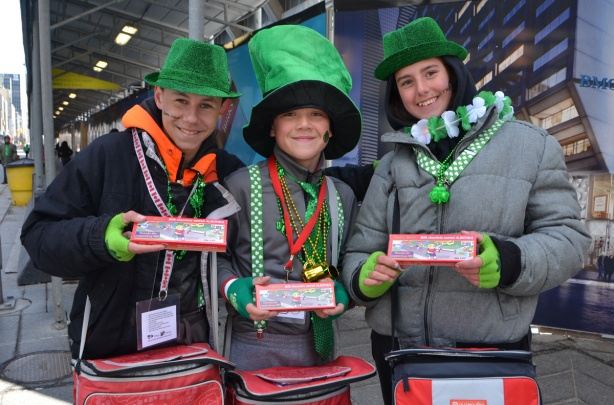three teenagers selling candy at the parade, all dressed in green hats and other St. Patricks day stuff,