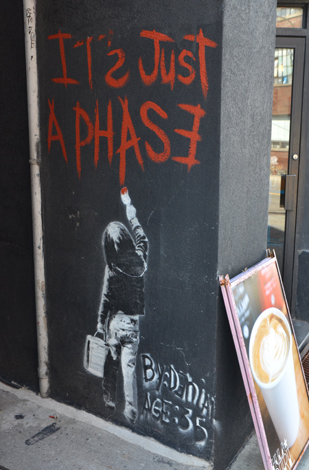 street art of a young person writing on the wall with red letters that say it's just a phase