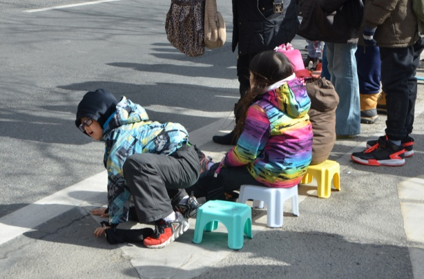three kids sitting on little plastic stools watching a parade,
