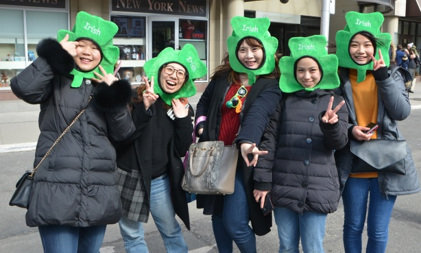 5 Asian women (Korean?) watching St. Patricks day parade, posing for the camera, all with shamrock green things aon their heads so only their faces stick out, the word Irish is written on each shamrock