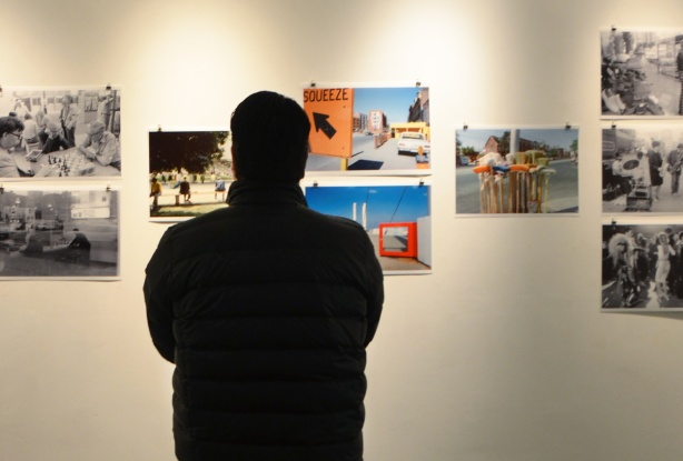the back of a man looking at a wall in a gallery, old photos of Toronto