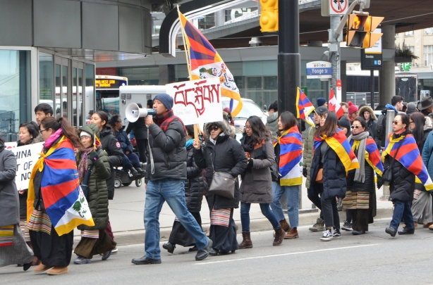 protesters walk up Yonge Street with Tibetan flag and signs, one man has a megaphone