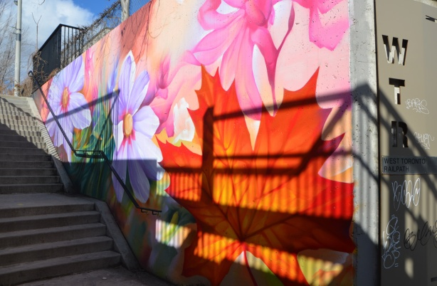 colourful mural outside beside a staircase, large flowers and leaves including an orange maple leaf