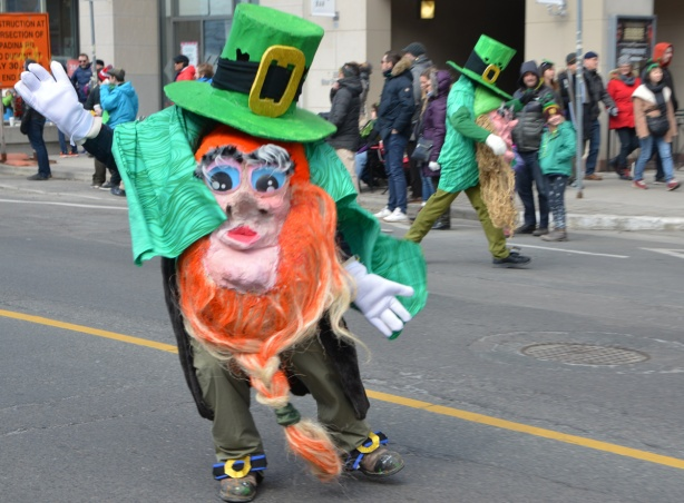 a man in a leprechauin costume walking in a parade.