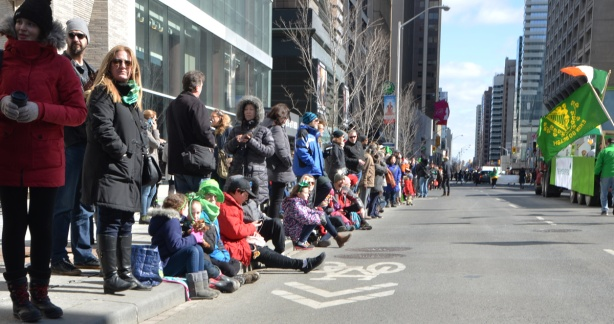 a group of people sitting on the sidewalk as a parade passes by on Bloor Street in Toronto