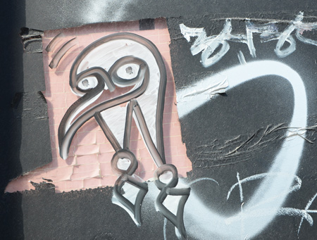 graffiti on a black wall, white bird like head on pick square
