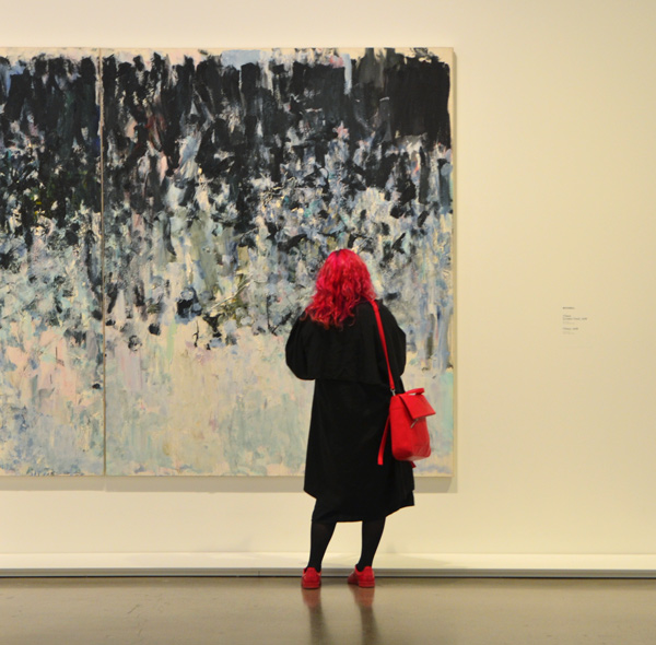 A woman in dark bright pink hair, with matching purse and shoes stands in front of a large painting by Joan Mitchell in an art gallery