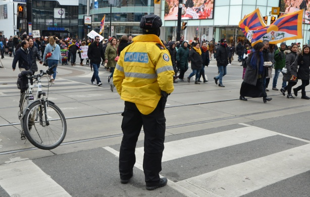a police man, with back tothe camera, stands in the middle of the street to block traffic as a Free Tibet march passes by on Yonge Street, protesters with flags and signs,