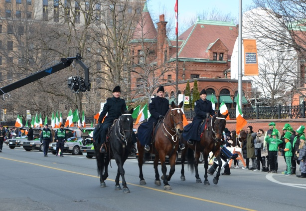 three toronto policemen on horseback at the front of a parade, as theypass by the press and a large microphone boom