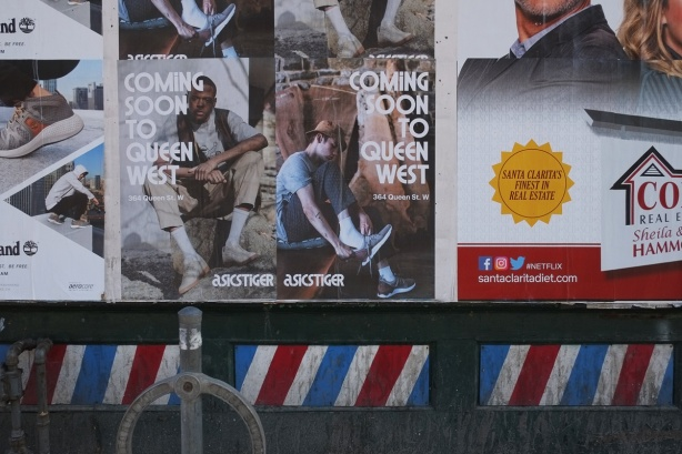posters on an empty building, exterior wall, bottom of wall has barber pole stripes painted on it.