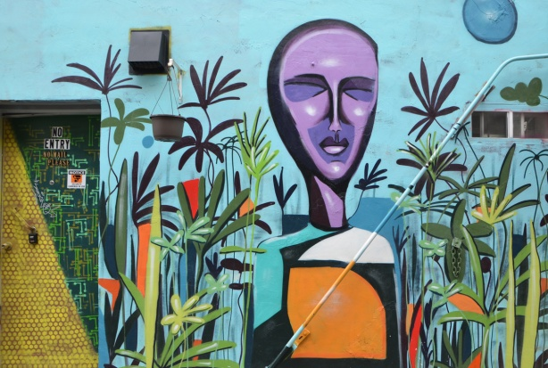 mural of a head and shoulder of a young man, by P.S., in an alley, purple face, beside a door that has street art on it too