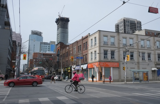 the intersection of Queen and Jarvis, looking northwest, with a foodora cyclist in pink in the intersection, traffic, street car, and in the distance, development on Yonge and westward, cranes, glass towers