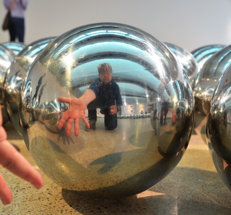 reflections of a person in a few shiny silver balls