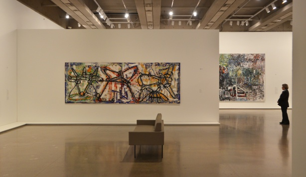 an emptry art gallery room except for a security guard standing on one side, a brown couch is in the middle of the room and a large abstract painting by Riopelle is one one wall, you can see into the next room where there is also a painting on a wall.