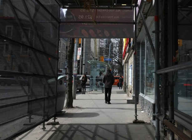 a man walks through a covered sidewalk, past a construction site and towards a bus shelter