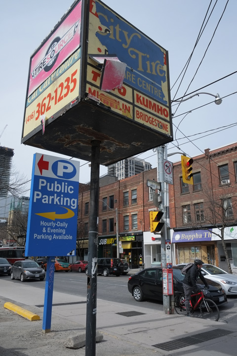large blue public parking sign, also a large box shaped sign on a tall pole. The sign is wearing out