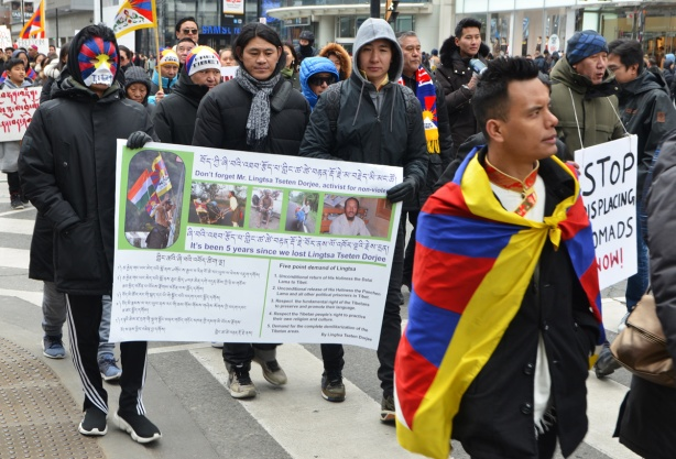 a group of young men marching in a protest, Free tibet. carrying a banner with a lot of words in both Tibetan and English, one is wrapped in a Tibetan flag, some are wearing free tibet hats,