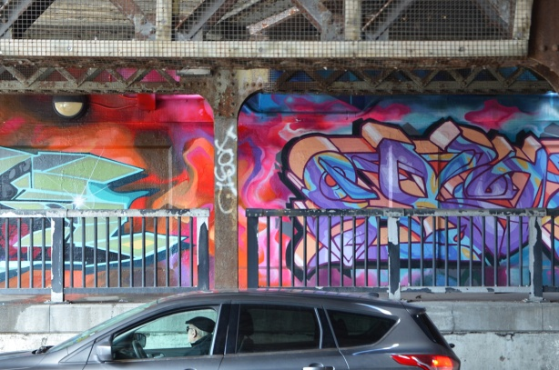 car stopped in traffic under railway bridge, driver is looking at the mural that is painted under the underpass