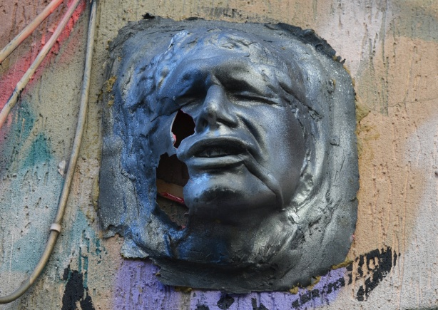 a three D sculpture of a man's face, on a wall, outside, graffiti, forlorn expression on his face