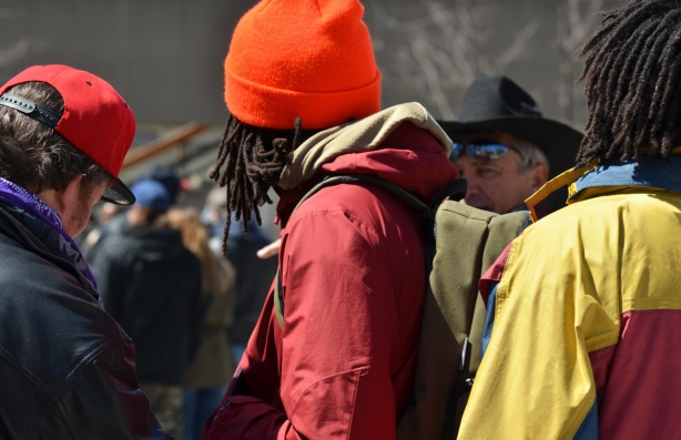 three men with dreadlocks and bright coloured toques, backs to camera, over one shoulder is an older man looking close to the camera