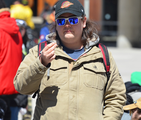 a man in a beige jacket, blue sunglasses and black baseball cap smokes a joint outside