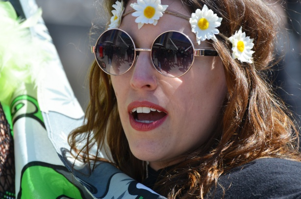 a woman with a head band made of rope and fake daisies, wears round sunglasses, mouth with red lipstick, partially open and talking,
