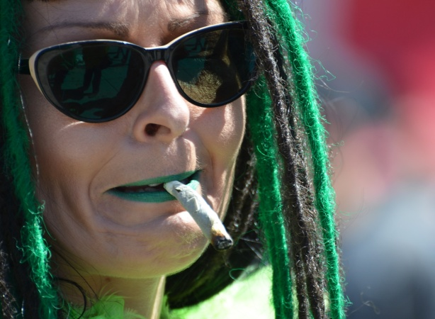 woman with dark sunglasses and black and green dreadlocks smokes a joint, close up photo of her face