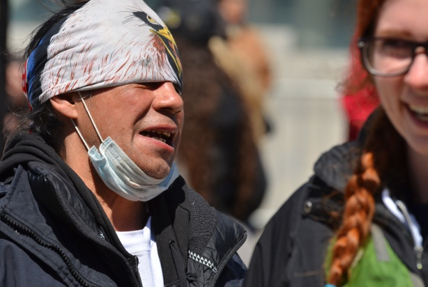 Indigenous man with cap on his head and medical mask under his chin, makes a face, a red head woman in on the right, partially cropped out and out of focus, she is laughing