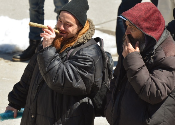 two men in black parkas, outside, one has a very large marijuana cigarette in his mouth although it is not yet lit;