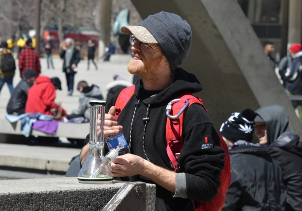 a young man with black hoodie, stands outside at Nathan Phillips square with a bong in his hand, smiling, 420 day event