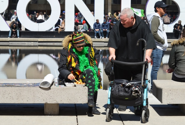 a woman in green and clothes with marijuana leaves on them, sits on a bench at Nathan Phillips, a man in a walker is beside her and talking to her.