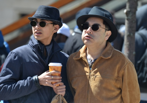 two men in black fedoras, one is holding a cup of coffee, outside, jackets on