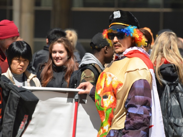 a man with multicoloured curly wig and police cap holds a banner (backside to the camera) that some people are reading