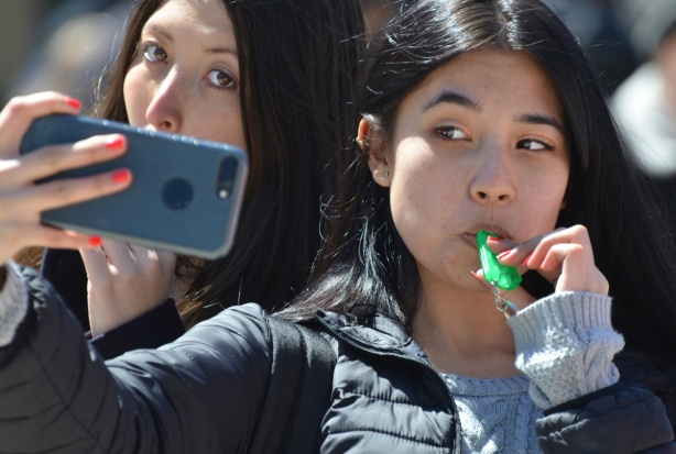 two young women taking a selfie, one is blowing on a green whistle