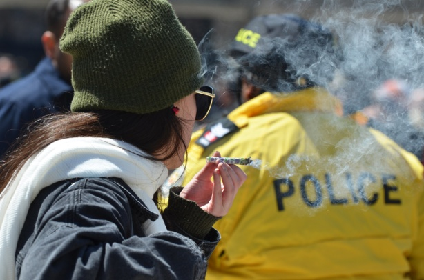 a woman in a green hat smokes a joint behind the back of a policeman in a yellow jacket.