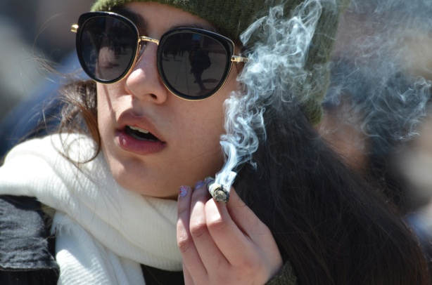 a young woman with sunglasses and a white scarf around her neck smokes a joint,