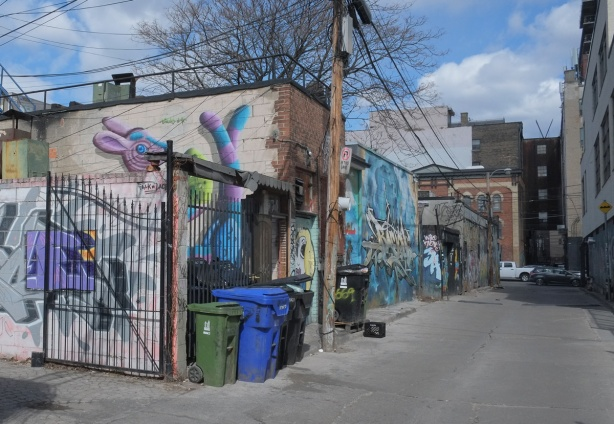 alley with low buildings, lots of graffiti and street art