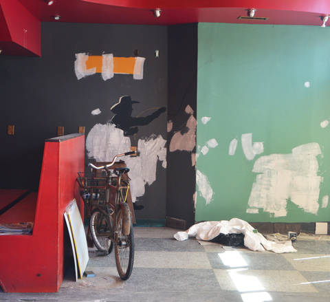 looking in the window of an empty restaurant, green and black walls, red bench, bike, top part of a silhouette of a cowboy on the wall