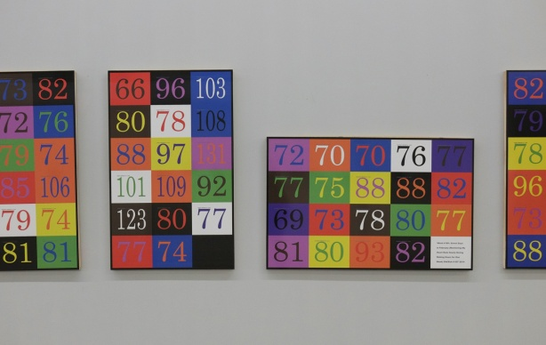 Part of a set of 7 paintings by Bruce Eves on a gallery wall, each painting is squares with numbers in them. The numbers are Eves' heart rate taken every hour for a week.