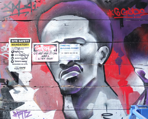 mural of a black man in purples and reds on a concrete block wall, with three signs posted on his face