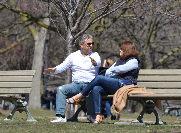 an older couple sitting on a bench in a park, talking to each other, the man is using his arms expressively