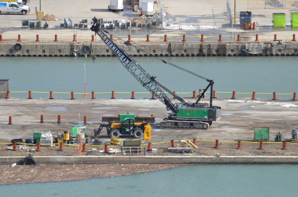 a mobile crane on tractor wheels, green body, is helping dig a hole in the ground on a flat piece of land that has water on two sides. lots of orange and black construction cones around the piece of land